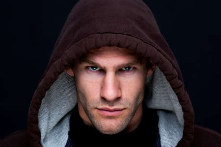 hooded top: Headshot of a man wearing a brown hooded top with an intense stare