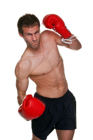 Male boxer delivering an uppercut punch, isolated on white background. This shot has a small amount of motion blur.