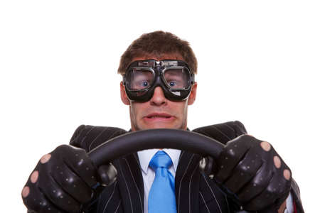 Businessman in driving gloves and goggles with a look of panic on his face, isolated on white background.