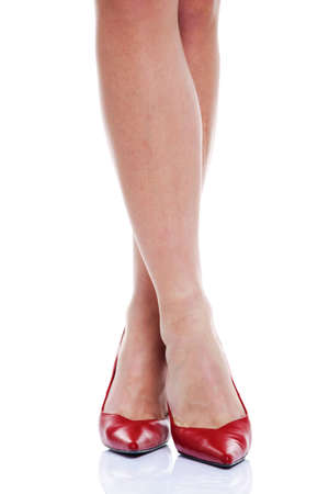 highheeled: A womans piernas y zapatos de tac�n alto de color rojo sobre fondo blanco aisladas.
