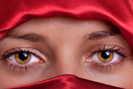 veil: Close up of a pair of beautiful female brown eyes framed by a red silk veil.