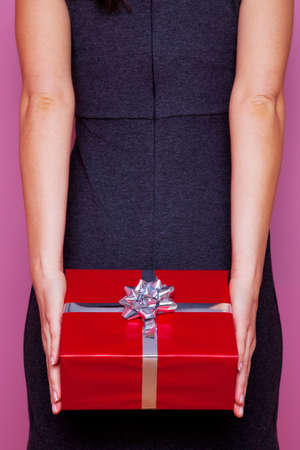 Woman holding a surprise present behind her back, pink background Stock Photo - 4906144
