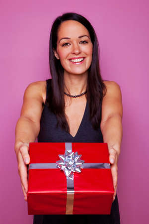 Attractive brunette woman giving you a present in red wrapping paper with silver ribbon and bow. Stock Photo - 4906160