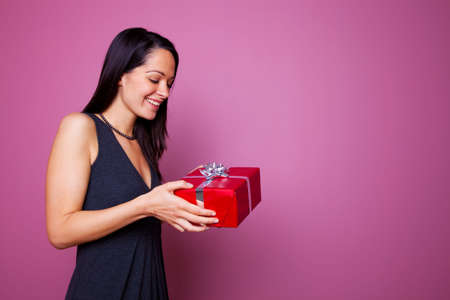 Woman smiling as she receives a present wrapped in red wrapping paper with silver ribbon and gift bow. photo