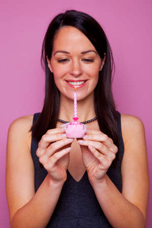 Happy brunette woman holding a small birthday cake with candle on pink background Stock Photo - 4906145