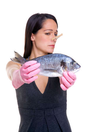 A woman holding a fish at arms length whilst wearing pink rubber gloves and a clothes peg on her nose. Isolated on white background, focus on the fish. Stock Photo