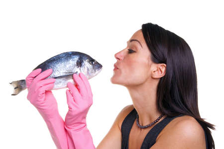 Woman in pink rubber gloves about to kiss a fish, isolated on white background. photo