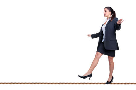 tightrope: Businesswoman walking along a tightrope, isolated on a white background.