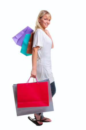 Blond woman carrying colorful shopping bags, isolated on a white background. photo