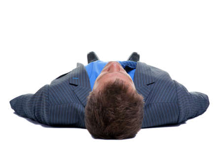 lay down: Businessman in suit and tie lying on his back viewed from his head at a low angle, isolated on a white background. Stock Photo