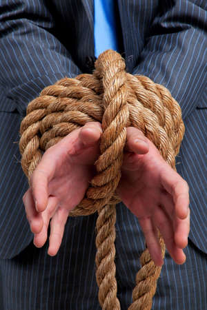 Close up of a businessmans hands tied with rope photo