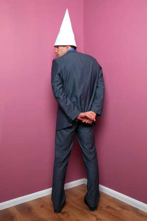 scolded: A businessman standing in the corner whilst wearing a dunce hat. Stock Photo