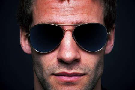 rimmed: Close up retrato de un hombre vestido de oro ala aviador gafas de sol Foto de archivo
