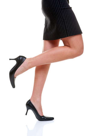 womens clothing: Womans legs wearing a short pinstripe skirt and black high heel shoes, on a white background. Stock Photo