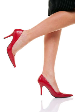 A womans legs with red high heel shoes on a white background.