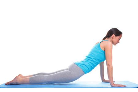 pilate: Une brunette femme faisant des exercices d'�tirement sur un tapis de yoga, isol� sur un fond blanc.