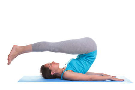 A brunette woman lying on a yoga mat doing a leg stretch excercise, isolated on a white background. Stock Photo
