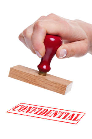 Hand holding a rubber stamp with the word Confidential photo
