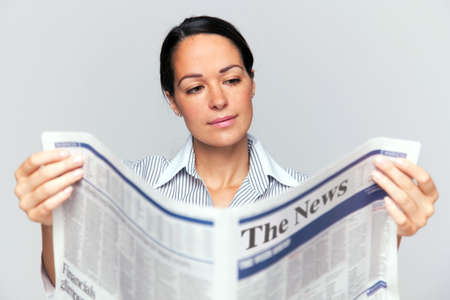 newspaper read: Businesswoman reading a newspaper, focus is on her face and newspaper is blurred. Stock Photo