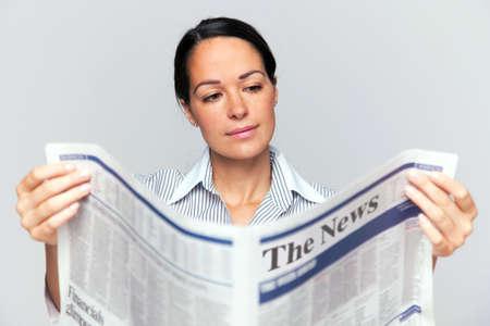 broadsheet newspaper: Businesswoman reading a newspaper, focus is on her face and newspaper is blurred. Stock Photo