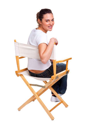 Brunette model sat in a directors chair looking back over her shoulder, isolated on white. Add your own text to the back of the chair. photo