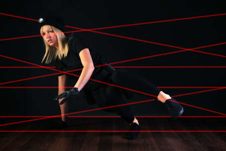 Blond cat burglar climbing through a laser beam alarm system. photo