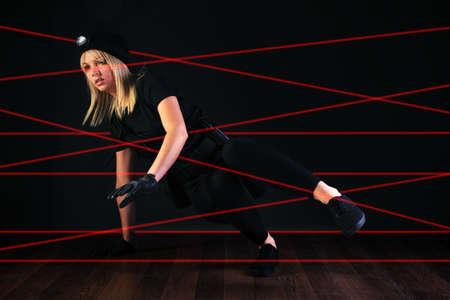perpetrator: Blond cat burglar climbing through a laser beam alarm system. Stock Photo