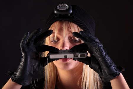 spy camera: Blond woman cat burglar taking a photo with a spy camera