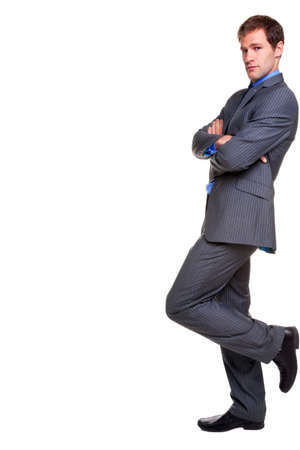 stood: Businessman in a pinstripe suit leaning with his arms folded, looking at camera, isolated on a white background. Stock Photo