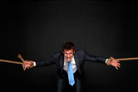 struggling: Businessman struggling as hes pulled by rope attached to his wrists on both sides, dark background. Stock Photo