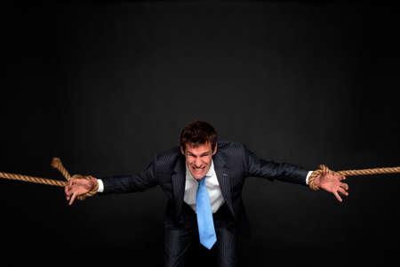tug o war: Hombre de negocios que luchan como �l es arrastrado por la cuerda adjunta a las mu�ecas de ambas partes, fondo oscuro.