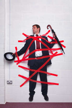 傘とボウラーの帽子を保持しているビジネスマンは赤いテープで壁に立ち往生。 写真素材