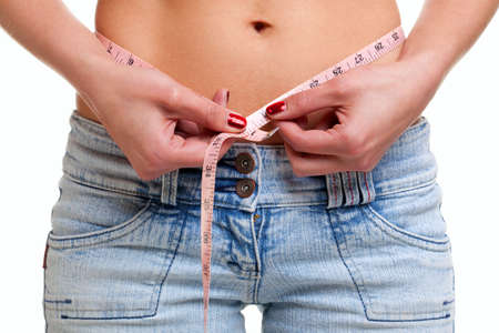 Close up of a woman measuring her waist with a pink tape measure, isolated on a white background. photo