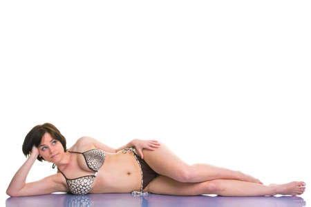 Brunette woman in a bikini lying on her side and looking upwards towards any text you wish to add, isolated on a white background. photo