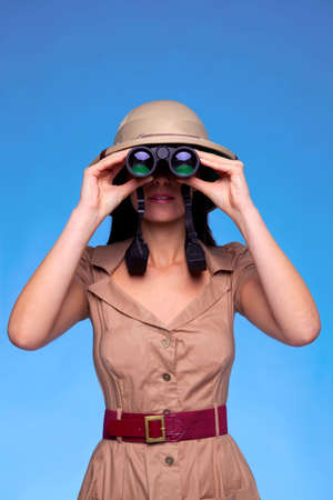 A woman wearing a pith helmet searching with a pair of binoculars, blue background with copy space. Stock Photo - 5179556