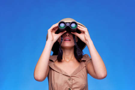pith: A woman wearing a pith helmet searching with a pair of binoculars, blue background with copy space. Stock Photo
