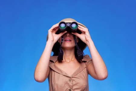 m�dula: Una mujer que llevaba un casco de m�dula b�squeda con un par de binoculares, fondo azul con copia espacio. Foto de archivo