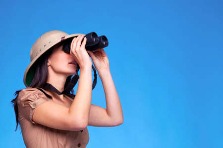pith: A woman wearing a pith helmet looking through a pair of binoculars, blue background with copy space. Stock Photo