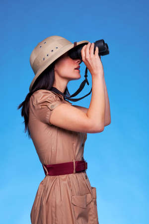 A woman wearing a pith helmet searching with a pair of binoculars, blue background with copy space. photo