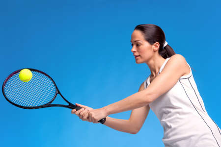 A brunette woman playing tennis against a blue background. photo