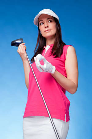 fashon: Woman golfer holding a driver and golf ball