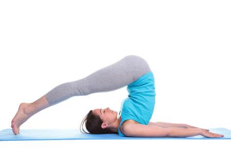 buena postura: Mujer acostada de espaldas sobre una colchoneta en el ejercicio de una posici�n de yoga los pies sobre su cabeza, aislada sobre un fondo blanco. Foto de archivo