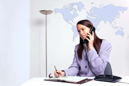 A businesswoman on the telephone sat at a desk in her office writing in her diary, world map on the wall behind her. photo