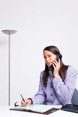 Businesswoman talking on the telephone whilst sat at her office desk , copy space abover her head. Stock Photo - 5179531