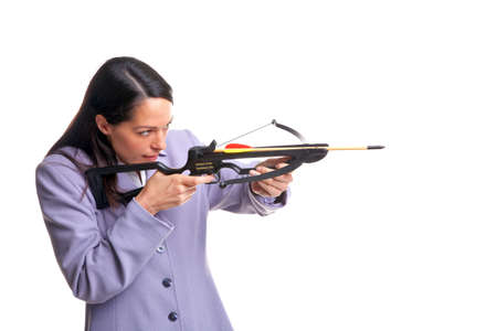 crossbow: Businesswoman in a suit shooting an arrow from a crossbow as she aims at the target, isolated on a white background. Stock Photo
