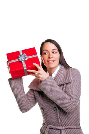 Brunette woman shaking her present to see whats inside, isolated on a white background. photo
