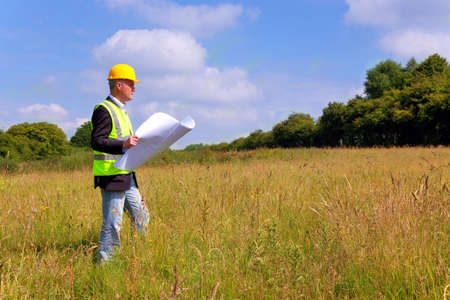 surveyor: Architect wearing site safety gear and holding plans surveying a new building plot