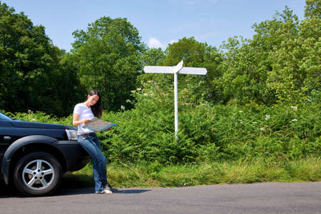 A woman leaning on her car as she reads a map next to a roadside sign, the sign is blank for you to add your own text. photo