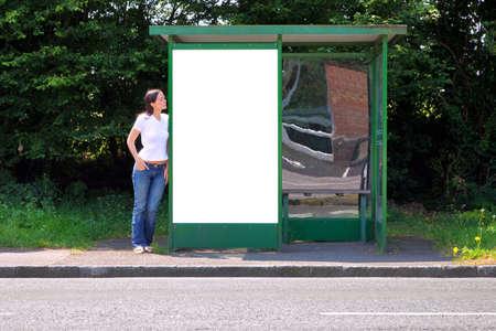 fermata bus: Una donna in piedi in un paesaggio rurale alla fermata del bus pendente su un rifugio con un cartellone bianco.
