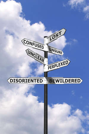 Concept image of words associated with being Lost and Confused on a  signpost against a blue cloudy sky. Stock Photo